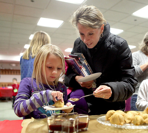 Leslie Olson helps her daughter, Alyssa, 6, with an Indian samosa snack as part of the Geneva Public Library's Passport Program about India Tuesday afternoon.