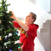 Jenny Scara of Batavia decorates a Christmas tree at one of the homes at Marklund's Geneva campus Friday morning.