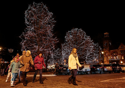 Kyle Grillot - kgrillot@shawmedia.com   Pedestrians cross North Johnson Street during the Lighting of the Square Friday in Woodstock.