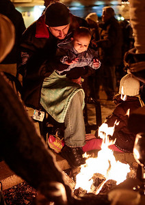 Kyle Grillot - kgrillot@shawmedia.com   Michael Kniesel of McHenry warms up with his daughter Charlotte, 1, during the Lighting of the Square Friday in Woodstock.