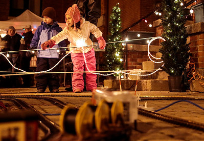 Kyle Grillot - kgrillot@shawmedia.com   Chase Jarvis, 5, and his sister Paige Jarvis, 5, both of Woodstock watch a model train pass during the Lighting of the Square Friday in Woodstock.