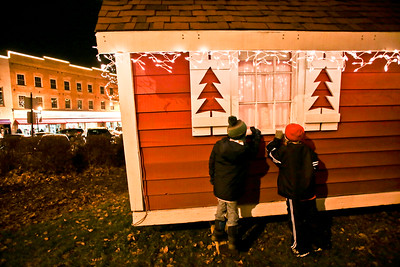 Michelle LaVigne/ For Shaw Media Nine-year-old John Leask of Oakwood Hills (right,) and five-year-old Cooper Doson of West Dundee, try to get a look inside of Santa's home, located on Woodstock square during the holiday lighting event on Friday, November 27th, 2015.