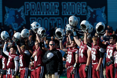 Prairie Ridge head coach Chris Schremp center stands as his players raise their helmets before their Class 6A quarterfinal playoff game against Lake Forest at Prairie Ridge High School on Saturday, November 12, 2016 in Crystal Lake, Ill. The Wolves defeated the Scouts 71-7.  John Konstantaras photo for the Northwest Herald