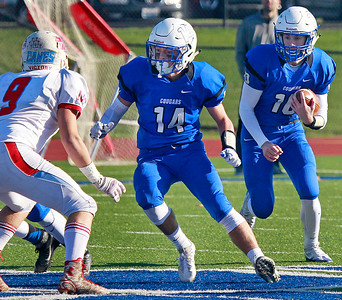 Candace H. Johnson – For Shaw Media Vernon Hills Max Lyle protects quarterback Kyle Hull as he runs the ball against Marion Central's Steve Pinter in the second quarter during the Class 5A state quarterfinal game at Vernon Hills High School.