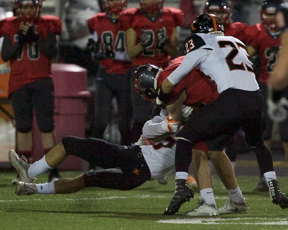 St Charles East's Nicholas Garlisch (7) and Sebastian Grohe (23) tackle Palatine for the stop on Nov. 12 at the Class 8A Playoff game in Palatine.