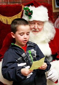 Candace H. Johnson-For Shaw Media Nathaniel Redmond, 7, of Antioch shows Santa his Christmas list at Santa's Frozen Village in downtown Antioch.