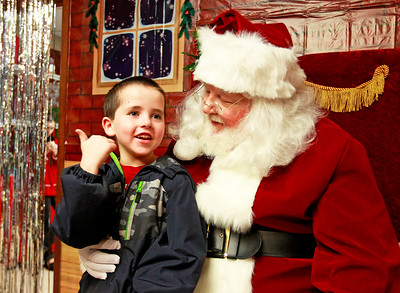 Candace H. Johnson-For Shaw Media Nathaniel Redmond, 7, of Antioch talks with Santa about his brother, Christopher, at Santa's Frozen Village in downtown Antioch.