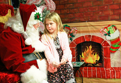 Candace H. Johnson-For Shaw Media Scarlett Towry, 7, of Trevor, Wis., talks to Santa at Santa's Frozen Village in downtown Antioch.
