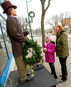 Candace H. Johnson-For Shaw Media Kinsey Delgado, 11, of Antioch and her mother, Tracey, look at Joyful Fred from the Dickens Holiday Village in downtown Antioch.