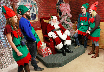 Candace H. Johnson-For Shaw Media Rachael Abendroth, 15, of Ingleside shares a laugh with Santa and the other Elves at Santa's Frozen Village in downtown Antioch.