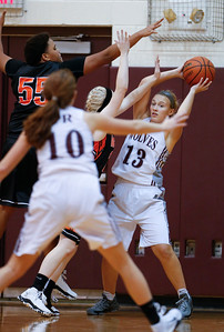 Madison Ljunggren (13) of Prairie Ridge looks to pass as Avalon Henderson (55) and Julia Rice (20) of McHenry defend during the fourth quarter of their game at Prairie Ridge High School on Tuesday, November 29, 2016 in Crystal Lake. The Warriors defeated the Wolves 49-38.  John Konstantaras photo for the Northwest Herald
