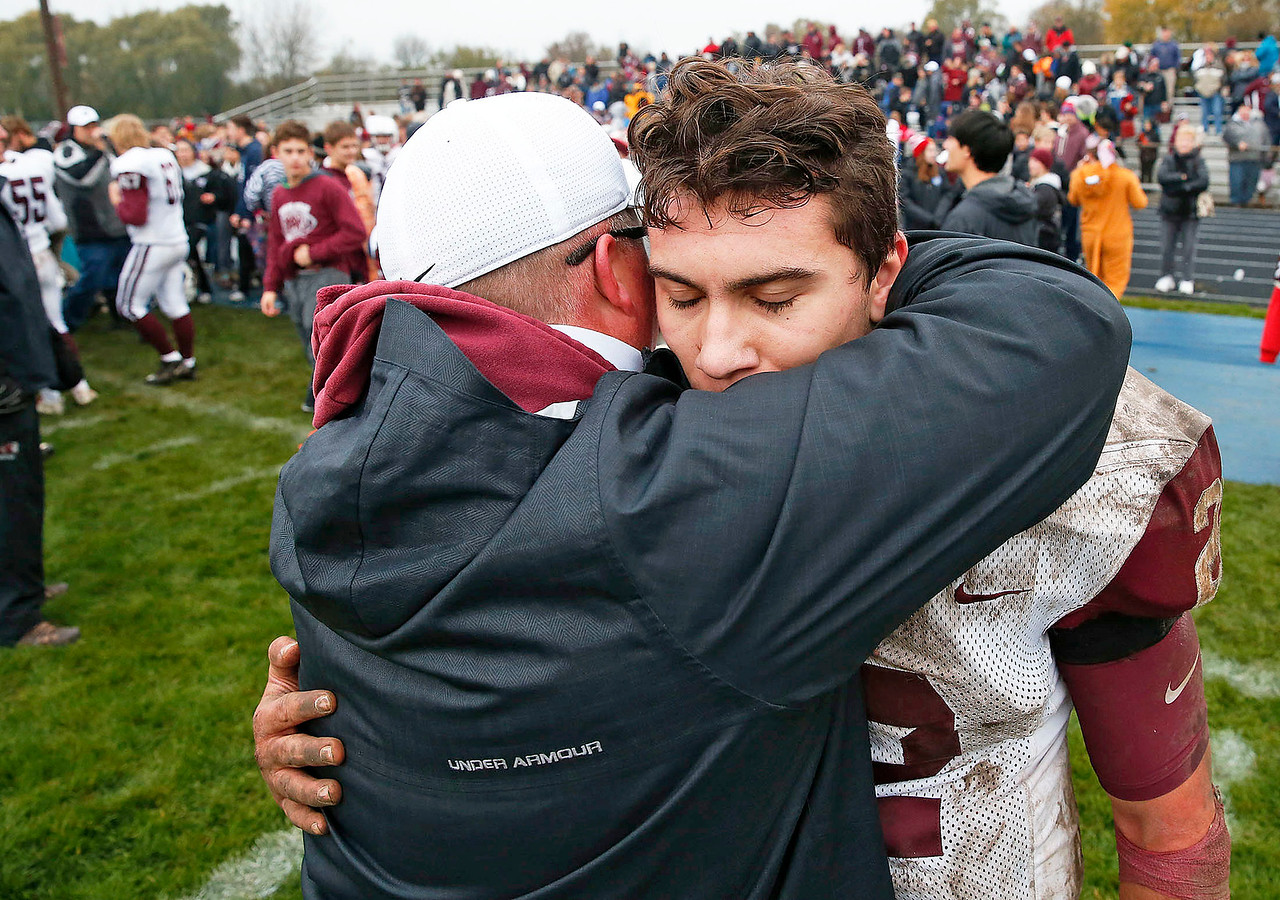 Prairie-Ridge head coach Chris Schremp hugs Samson Evans (22) after the defeated Cary-Grove 17-3 in their IHSA Class 6A playoff game at Cary-Grove High School on Saturday, November 4, 2017 in Cary, Illinois.  John Konstantaras photo for Shaw Media