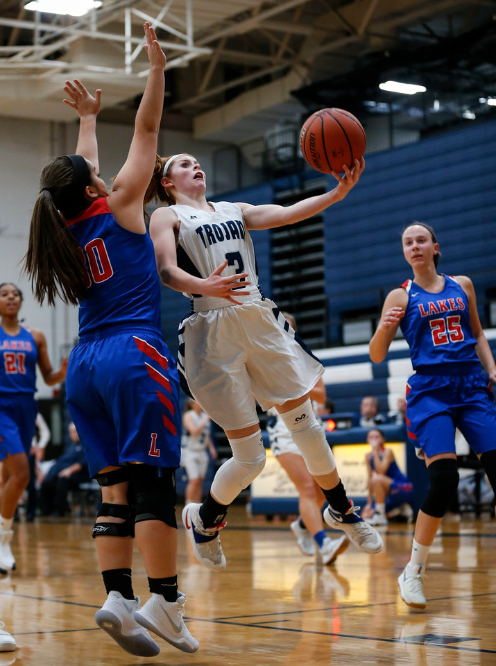 Bailey Steinkamp (3) from Cary-Grove scores as she drives by Abigail Korjenek (30) from Lakes during the second quarter of their game at Cary-Grove High School on Monday, November 13, 2017 in Cary, Illinois. The Trojans defeated the Eagles 47-22. John Konstantaras photo for Shaw Media