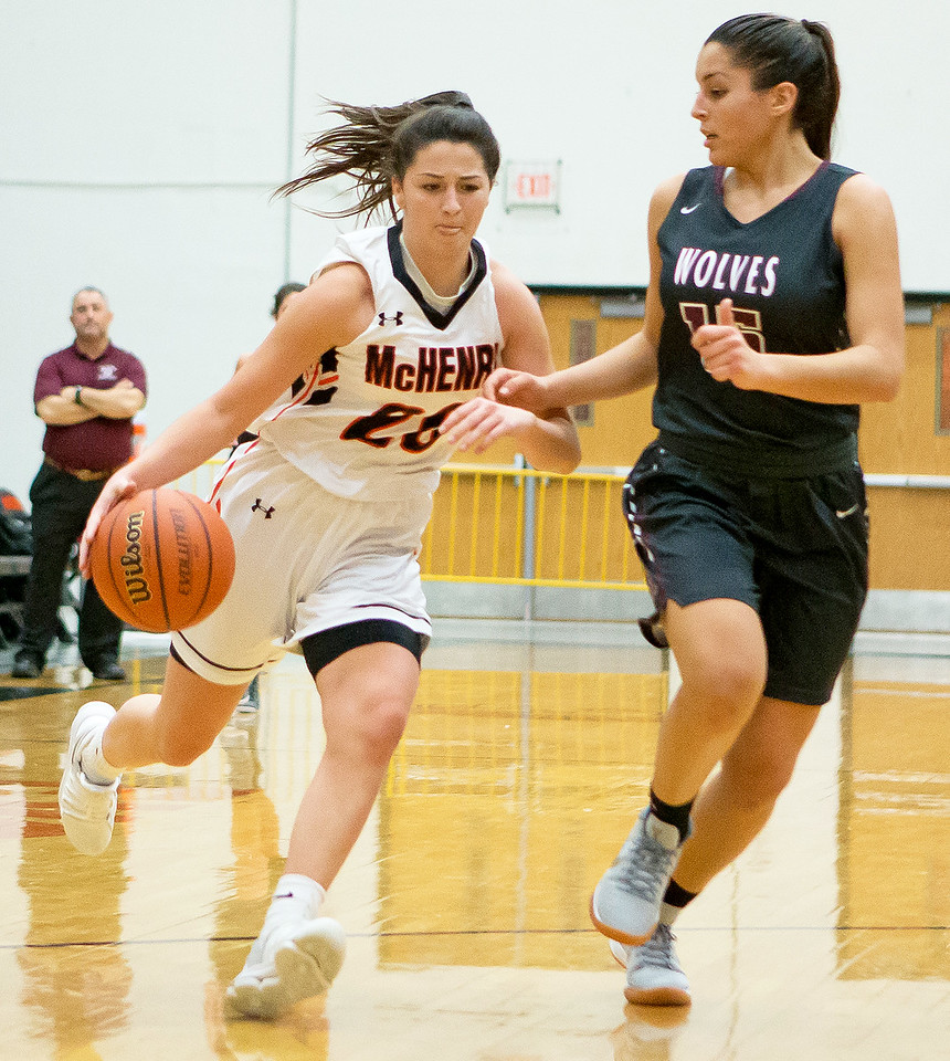 McHenry's Ava Interrante (L) drives past Prairie Ridge defender Nicole Dorn Tuesday, November 28, 2017 in McHenry. McHenry wins 68-56 with Interrante finishing with 13pts. KKoontz – For Shaw Media