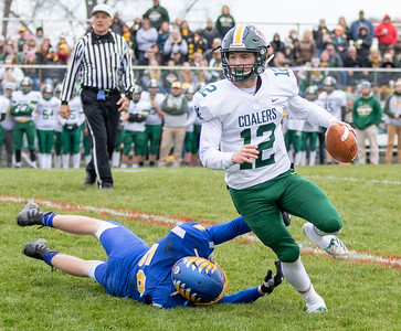 Coal City quarterback Payton Hutchings eludes a tackle by Johnsburg's  Eric Johnson Saturday, November 3, 2018 in Johnsburg. Coal City went on to win the Class 4A second-round playoff game 33-14 and will face Richmond-Burton next week. KKoontz – For Shaw Media
