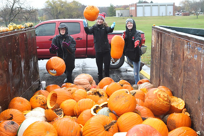 Candace H. Johnson-For Shaw Media Volunteers Nicole Roth, Kate Hay, both 17, and Megan Rastrelli, 18, all of Mundelein and in the National Honor Society at Mundelein High School, throw pumpkins into a dumpster to be used for compost during the Mundelein Park & Recreation District's Annual Pumpkin Drop at Keith Mione Community Park in Mundelein. The pumpkins were sent to Midwest Organics Recycling, out of Wauconda.(11/4/18)