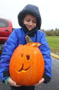Candace H. Johnson-For Shaw Media Landon Van Arsdale, 7, of Mundelein holds his carved pumpkin he is about to throw into a dumpster to be used for compost during the Mundelein Park & Recreation District's Annual Pumpkin Drop at Keith Mione Community Park in Mundelein. The pumpkins were sent to Midwest Organics Recycling, out of Wauconda.(11/4/18)