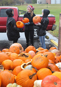 Candace H. Johnson-For Shaw Media Volunteers Nicole Roth, Kate Hay, both 17, and Megan Rastrelli, 18, all of Mundelein and in the National Honor Society at Mundelein High School, share a laugh before throwing pumpkins into a dumpster to be used for compost during the Mundelein Park & Recreation District's Annual Pumpkin Drop at Keith Mione Community Park in Mundelein. The pumpkins were sent to Midwest Organics Recycling, out of Wauconda.(11/4/18)