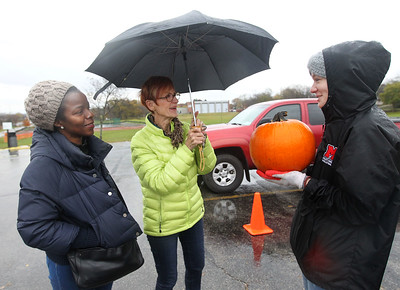 Candace H. Johnson-For Shaw Media Fiona Mensah and Rita O'Connor, both of Long Grove talk with Megan Rastrelli, 18, of Mundelein after handing her their pumpkin to be turned into compost during the Mundelein Park & Recreation District's Annual Pumpkin Drop at Keith Mione Community Park in Mundelein. All of the pumpkins collected during the event were sent to Midwest Organics Recycling, in Wauconda. (11/4/18)