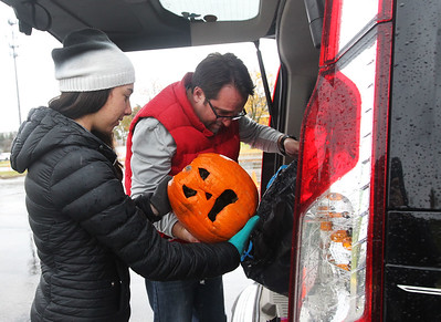Candace H. Johnson-For Shaw Media Volunteer Jessica Reisman, 17, of Mundelein helps Jim Kallieris, of Libertyville take a pumpkin out of his trunk to be used for compost during the Mundelein Park & Recreation District's Annual Pumpkin Drop at Keith Mione Community Park in Mundelein. The pumpkins were sent to Midwest Organics Recycling, out of Wauconda.(11/4/18)