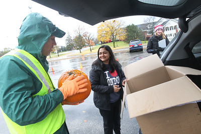 Candace H. Johnson-For Shaw Media Compost specialist Vytas Pabedinskas, of Grayslake takes a pumpkin from Neha Dubal, of Vernon Hills, to be put into a dumpster for compost during the Mundelein Park & Recreation District's Annual Pumpkin Drop at Keith Mione Community Park in Mundelein. The pumpkins were sent to Midwest Organics Recycling, out of Wauconda.(11/4/18)
