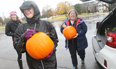 Candace H. Johnson-For Shaw Media Kate Hay, of Mundelein watches Nicole Roth, of Hawthorn Woods, both 17, help Deanne Liebert, of Waukegan take pumpkins from her trunk to the dumpster to be used for compost during the Mundelein Park & Recreation District's Annual Pumpkin Drop at Keith Mione Community Park in Mundelein. The pumpkins were sent to Midwest Organics Recycling, out of Wauconda.(11/4/18)