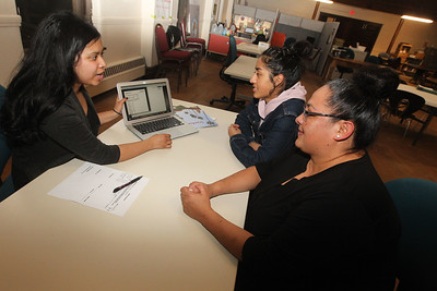 Candace H. Johnson-For Shaw Media Daisy Hernandez, program associate, talks with Gabriela Serna, 15, and her mother, Maribel, all of Waukegan about how to access Gabriela's unofficial transcript online through her high school during their monthly meeting at Waukegan to College on the second floor at Christ Episcopal Church in Waukegan. (11/6/18)