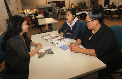 Candace H. Johnson-For Shaw Media Daisy Hernandez, program associate, shows college brochures to Gabriela Serna, 15, with her mother, Maribel, sitting close by during their monthly meeting at Waukegan to College on the second floor of Christ Episcopal Church in Waukegan. (11/6/18)