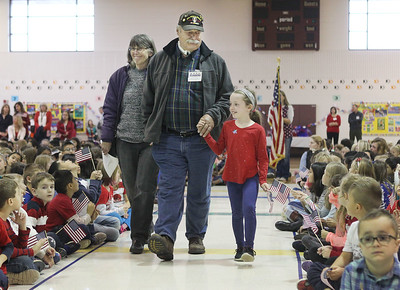 Candace H. Johnson-For Shaw Media Army veteran John Mann, of Deerfield (center) walks with his wife, Judy, and granddaughter, Madeline Ecker, 7, of Round Lake Beach, as he is recognized for his military service during the Veterans Day Celebration at the William L. Thompson Elementary School in Lake Villa. Madeline is a second-grade student at the school.(11/12/18)