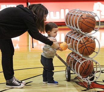 Candace H. Johnson-For Shaw Media Josy Bosworth, of Antioch hands her son, Weston, nineteen-months-old, his ball as he reaches for a bigger basketball while playing on the court at halftime as Grant plays Boylan during the Grant Boys Basketball Thanksgiving Tournament in Fox Lake. Weston is the son of Grant's head coach of varsity boys basketball, Wayne Bosworth.(11/19/18)