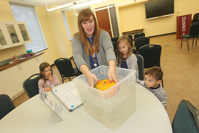 Candace H. Johnson-For Shaw Media Nicole Stocker, of Chicago, (center) museum educator, shows how a pumpkin can float as Lily Leivas, 4, of Great Lakes, Josie Frcka, 4, of Chicago and her brother, George, 2, watch the science experiment during Fall Family Fest at the Lake County Forest Preserves Bess Bower Dunn Museum in Libertyville. (11/17/18)