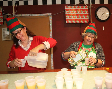 Candace H. Johnson-For Shaw Media Volunteer elves Heather Knight, of Gurnee and Karen Helms, of Grayslake pour drinks for visitors at the Oasis during Grayslake's Tree Lighting Festivities in downtown Grayslake. (11/23/18)