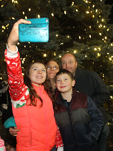 Candace H. Johnson-For Shaw Media Ellen Batty, 12, of Grayslake and her brother, Joseph, 9, take a family photo with their parents, Gemma and Chris in front of the holiday tree just lit up in Centennial Park during Grayslake's Tree Lighting Festivities in downtown Grayslake. (11/23/18)