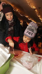 Candace H. Johnson-For Shaw Media Nancy Gonzalez, of Round Lake watches her daughter, Emily, 4, decorate a sugar cookie at the Oasis during Grayslake's Tree Lighting Festivities in downtown Grayslake. Something's Brewing, of Grayslake provided the cookies. (11/23/18)