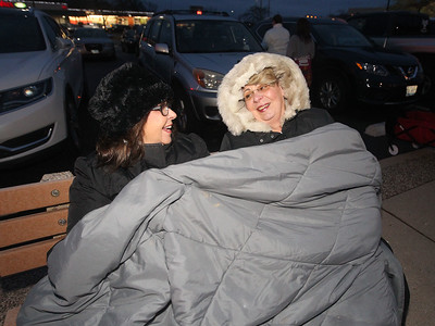 Candace H. Johnson-For Shaw Media Lori Vincent, of Hebron and Cindy Noga, of Round Lake Beach stay warm under a blanket on a cold night as they wait for the Fox Lake Festival of Lights Parade to begin on Grand Avenue. (11/24/18)
