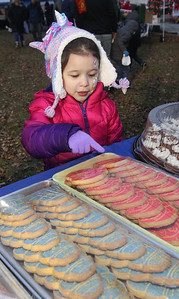 Candace H. Johnson-For Shaw Media Bella Osborn, 4, of Fox Lake points out which holiday sugar cookie she wants from Taste of Paris, of Mundelein at the Kris Kringle Winter Market at Community Garden Green during the Fox Lake Festival of Lights. Bella was at the market with her mother, Jennifer. (11/24/18)