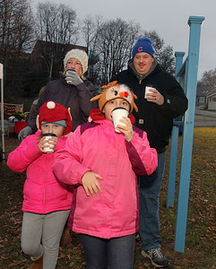 Candace H. Johnson-For Shaw Media Hillary and Chris Fries, of Ingleside walk with their daughters, Eleanor, 5, and Izabel, 7, drinking hot chocolate as they walk through the Kris Kringle Winter Market at Community Garden Green during Fox Lake Festival of Lights. (11/24/18)