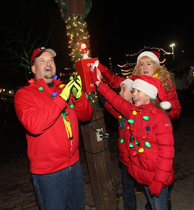 Candace H. Johnson-For Shaw Media Tim and Diane Foster, of Fox Lake and their children, Axton, 10, and twin sister, Tianna, flip the light switch to on as they light up Millennium Park at night at the Holiday Tree Lighting during Fox Lake Festival of Lights. (11/24/18)
