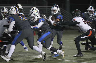 Candace H. Johnson-For Shaw Media Warren's Marc Davila tries to escape the tackle attempt by Plainfield East's Grant Perkins in the fourth quarter during the Class 8A first round state playoff game at Warren Township High School in Gurnee. Warren won 49-7.  (11/2/19)