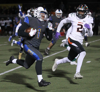 Candace H. Johnson-For Shaw Media Warren's Christian Phillips looks to outrun Plainfield East's Brian Tape as he carries the ball in the first quarter during the Class 8A first round state playoff game at Warren Township High School in Gurnee. Warren won 49-7.  (11/2/19)