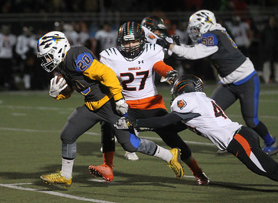 Candace H. Johnson-For Shaw Media Warren's Peara Savath runs the ball as he escapes the tackle attempt by Plainfield East's Ethan Urbanowicz and Charlie Wolf in the fourth quarter during the Class 8A first round state playoff game at Warren Township High School in Gurnee. Warren won 49-7.  (11/2/19)