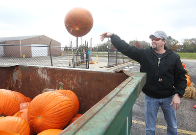 Candace H. Johnson-For Shaw Media Chris Braden, of Gurnee throws his pumpkin into a dumpster to be recycled into compost during Pumpkin Recycling & Fall Fun Day at Woodland Intermediate School in Gurnee. The pumpkins will go to Midwest Organics Recycling in McHenry to make compost. (11/2/19)