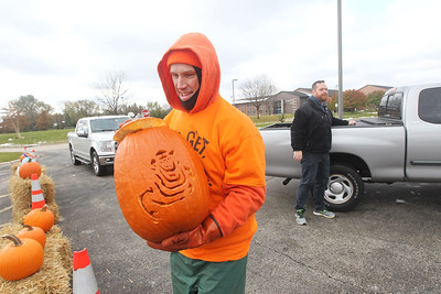 Candace H. Johnson-For Shaw Media Vytas Pabedinskas, of Grayslake, compost specialist with Save Our Soil Composting Solutions, carries a pumpkin to the dumpster for Jason Brauhn, of Gurnee as he collects pumpkins to be turned into compost during Pumpkin Recycling & Fall Fun Day at Woodland Intermediate School in Gurnee. The pumpkins will go to Midwest Organics Recycling in McHenry to make compost. (11/2/19)