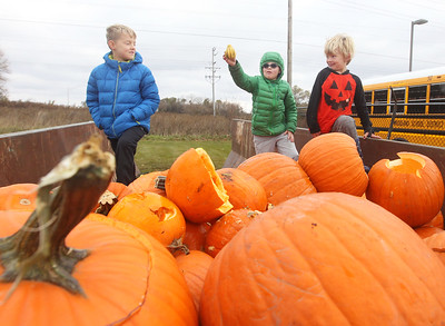 Candace H. Johnson-For Shaw Media Zack Moore, 9, of Gages Lake and his brothers, Erik, 9, and Liam, 7, check out the pumpkins and gourds in the dumpster donated to make compost during Pumpkin Recycling & Fall Fun Day at Woodland Intermediate School in Gurnee. The pumpkins will go to Midwest Organics Recycling in McHenry to make compost. (11/2/19)