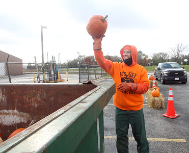Candace H. Johnson-For Shaw Media Vytas Pabedinskas, of Grayslake, compost specialist with Save Our Soil Composting Solutions, gets ready to throw a donated pumpkin into a dumpster to be turned into compost as he helps collect pumpkins during Pumpkin Recycling & Fall Fun Day at Woodland Intermediate School in Gurnee.  The pumpkins will go to Midwest Organics Recycling in McHenry to make compost. (11/2/19)