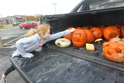 Candace H. Johnson-For Shaw Media Shayla Betke, 9, of Grayslake grabs one of her family's twenty-three pumpkins to be put into a dumpster for them to be made into compost during Pumpkin Recycling & Fall Fun Day at Woodland Intermediate School in Gurnee. The pumpkins will go to Midwest Organics Recycling in McHenry to make compost. (11/2/19)