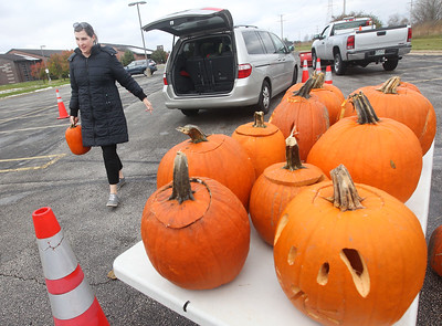 Candace H. Johnson-For Shaw Media Amy Eliason, of Gurnee carries her pumpkin to a dumpster during Pumpkin Recycling & Fall Fun Day at Woodland Intermediate School in Gurnee. All of the pumpkins collected will go to Midwest Organics Recycling in McHenry to make compost. (11/2/19)