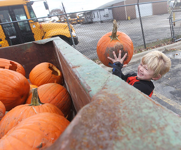 Candace H. Johnson-For Shaw Media Liam Moore, 7, of Gages Lake lifts his pumpkin into a dumpster for it to be turned into compost during Pumpkin Recycling & Fall Fun Day at Woodland Intermediate School in Gurnee. The pumpkins will go to Midwest Organics Recycling in McHenry to make compost. (11/2/19)
