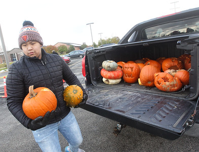 Candace H. Johnson-For Shaw Media Volunteer Paolo Robles, 15, of Waukegan carries pumpkins from the back of a truck to the dumpster during Pumpkin Recycling & Fall Fun Day at Woodland Intermediate School in Gurnee. The pumpkins will go to Midwest Organics Recycling in McHenry to be made into compost. (11/2/19)