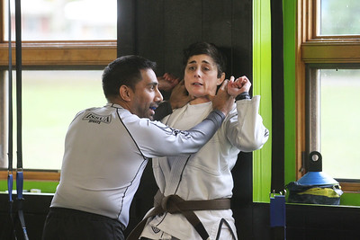 Candace H. Johnson-For Shaw Media Instructor Julie Bond, of Third Lake (on right) works with her assistant, Imran Faizi, of Lake Villa on showing her class self-defense techniques by grabbing hold of some of an attacker's fingers and bending them back during the Women's Self-Defense Seminar presented by Black Tiger Martial Arts at Prime Athletics in Grayslake.  (11/2/19)